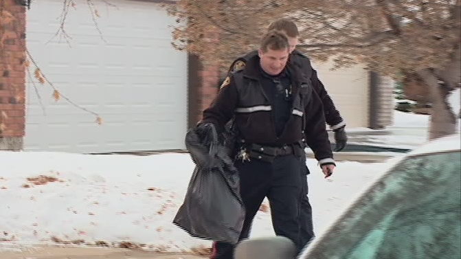 A Saskatoon police officer carries away the carcass of an injured coyote that was put down Sunday afternoon in the Silverwood Heights neighbourhood.