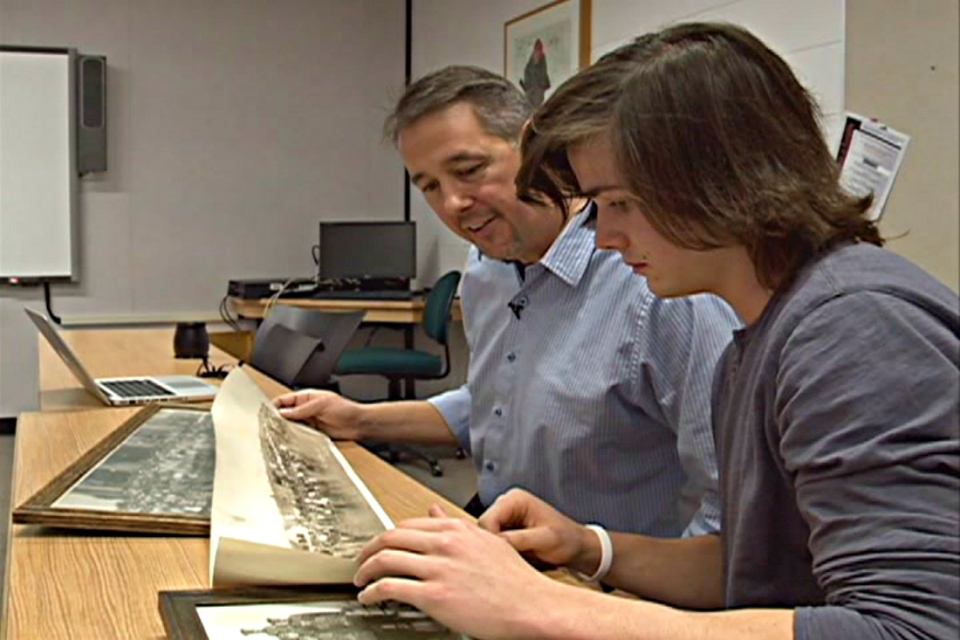 History professor Keith Carlson and history student Eric Story look at one of over 7,000 photos depicting Saskatchewan history collected by Adrian Paton.