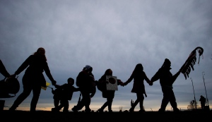 A group of First Nations protesters hold hands and dance in a circle during a demonstration in Surrey, B.C., in Jan. 2013. (Darryl Dyck / THE CANADIAN PRESS)