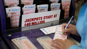 A woman prepares to choose her numbers on a lottery ticket Saturday, May 18, 2013, in the Chinatown district in Oakland, Calif. (AP / Ben Margot)