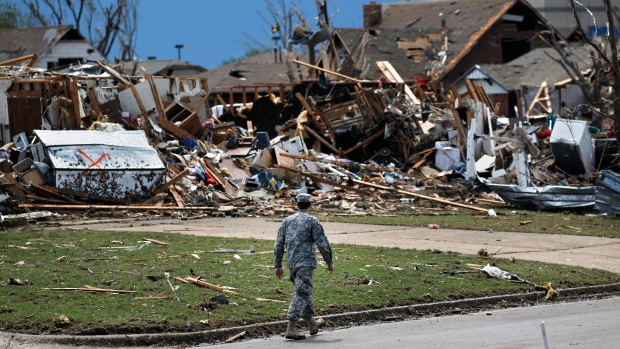 A soldier walks past the wreckage left when a tornado moved through Moore, Okla., Tuesday, May 21, 2013. (AP / Brennan Linsley)