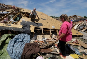 U.S. Air Force Staff Sgt. Jeremiah McDaniel, left, based at nearby Tinker Air Force Base prepares to hand Morgan Gregg, right, a porcelain Christmas decoration he recovered from a tornado damaged home, in Moore, Oklahoma, Wednesday, May 22, 2013. (AP / Tony Gutierrez)