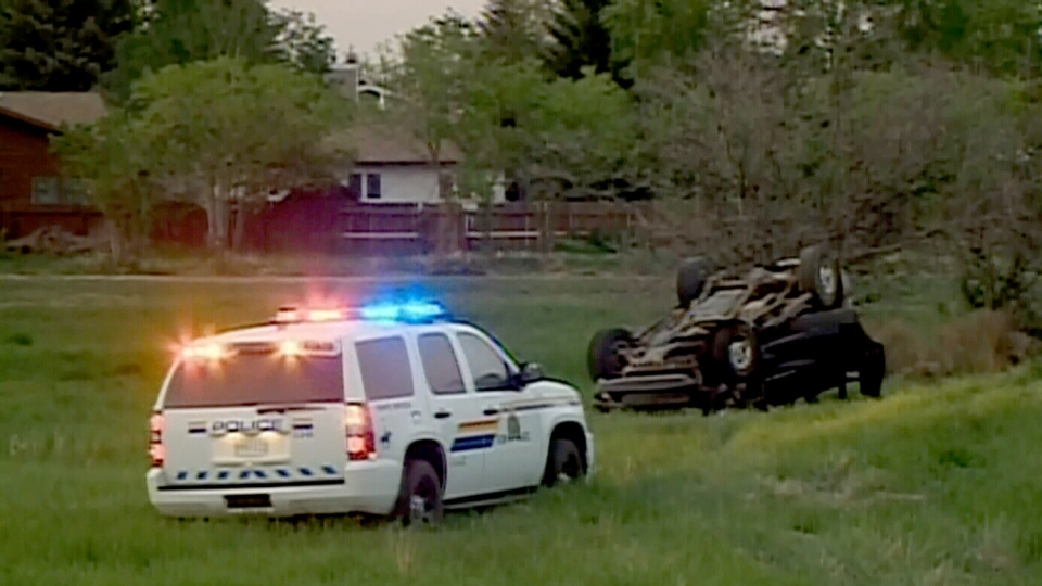 A police vehicle sits in the grass near an overturned car in Saskatoon, on Saturday, June 1, 2013. (CTV Winnipeg)