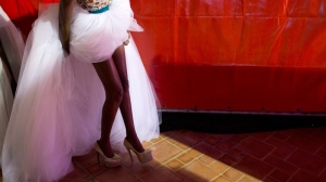 A model wearing a creation by Elie Kuame of Lebanon and Ivory Coast arranges her skirt behind her as she prepares to walk the runway at Hotel des Almadies, in Dakar, Senegal, Saturday, June 22, 2013. (AP Photo/Rebecca Blackwell)
