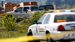 RCMP officers investigate the scene following a shooting at Western Forest Products in Nanaimo, B.C., Wednesday, April 30, 2014. (Chad Hipolito / THE CANADIAN PRESS)