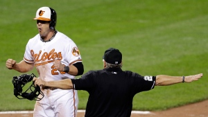 Baltimore Orioles' Steve Pearce, left, reacts as umpire Tom Hallion calls him safe at home plate on a single by J.J. Hardy in the sixth inning in the second baseball game of a doubleheader against the Pittsburgh Pirates, Thursday, May 1, 2014, in Baltimore. Baltimore won 6-5 in 10 innings. (AP / Patrick Semansky)