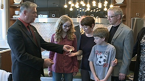 Caroll Thain, Martin Rempell, and their kids Matthew and Emily receive the key to their new home.
