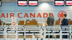 Passengers are photographed at an Air Canada check-in desk in Montreal in 2012. (Graham Hughes / THE CANADIAN PRESS)