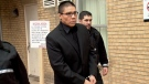 Blaine Taypotat is escorted from Saskatoon provincial court Thursday, Dec. 18, 2014 after pleading guilty to a fatal crash that killed a conservation officer.