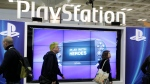 This March 8, 2012 file photo shows attendees walking past the Sony PlayStation PS Vita console on display in the Sony PlayStation booth at the Game Developers Conference in San Francisco. (Paul Sakuma / AP Photo)