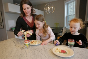 Kathy Burnett prepares a snack for her daughters Claudia, centre, and Sabina right, after their gymnastics class Thursday, Jan. 29, 2015, in Chicago. (AP Photo/M. Spencer Green)