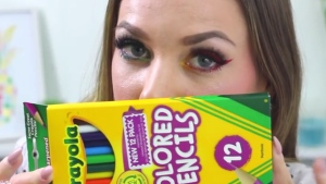 A woman holds up a box of the Crayola coloured pencils she used to create do-it-yourself eyeliner and lipstick. Crayola warned customers against using their product for makeup. (Rachelleea / YouTube)