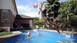 Julia Lowther, 12, reaches for a beach ball as parents Deb and Stuart look on in the family's backyard pool in Burlington, Ont., Sunday, June 1, 2014.  (Galit Rodan / THE CANADIAN PRESS)