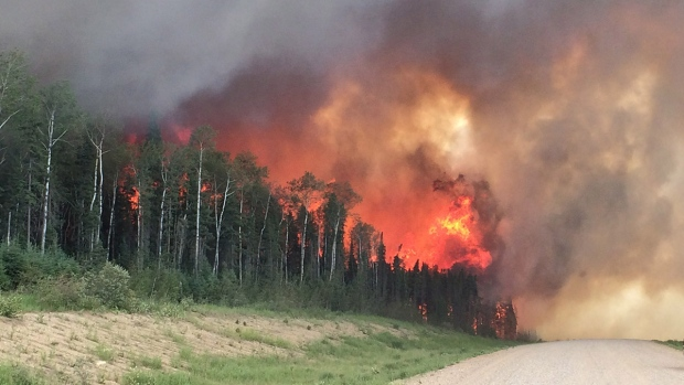 Forest fires throw flames above a tree-line along highway 969 in southern Saskatchewan on June 29, 2015. (Saskatchewan Ministry of Highways and Infrastructure)