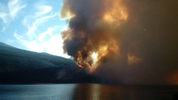 A wildfire rises over a hill in Jasper National Park on Thursday July 9, 2015. (Jasper National Park of Canada / THE CANADIAN PRESS)
