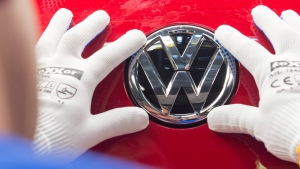 A worker checks the Volkswagen sign on a Golf car in Zwickau, eastern Germany, Sept. 6, 2015. (AP / Jens Meyer)