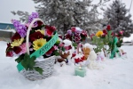 A memorial sits in front of the La Loche Community School in La Loche, Sask. on Sunday, Jan. 24, 2016. Four people were killed Jan. 22 in shootings at a local school and a home in the small town. THE CANADIAN PRESS/Jason Franson