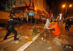 A rioter tries to throw a litter bin at police on a street in Mongkok district of Hong Kong, Tuesday, Feb. 9, 2016. (AP / Kin Cheung)