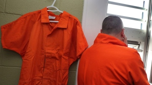 The orange jumpsuit that prisoners will wear at Her Majesty's Penitentiary in St. John's, Nfld., is seen inside the facility with an unidentified corrections officer on Thursday, March 24, 2016. THE CANADIAN PRESS/Paul Daly.