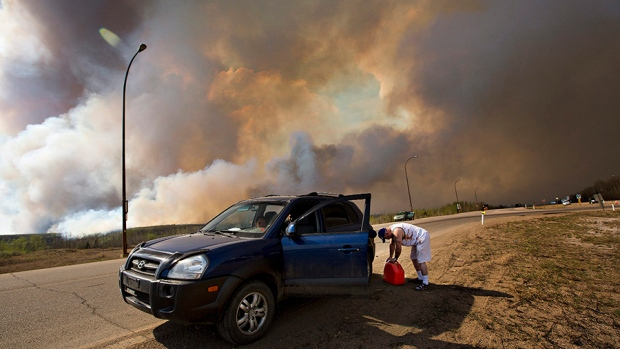 An evacuee puts gas in his car on his way out of Fort McMurray, Alberta, as a wildfire burns in the background Wednesday, May 4, 2016. (THE CANADIAN PRESS / Jason Franson)