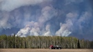 A semi truck drives away from a wildfire in Fort McMurray, Alta., on Thursday, May 5, 2016. (Jason Franson / THE CANADIAN PRESS)