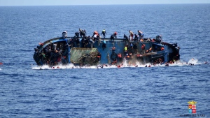 People jump off a boat moments before it overturns off the Libyan coast, Wednesday, May 25, 2016. (Marina Militare via AP)