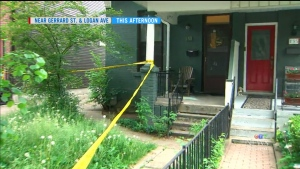 Police tape is placed around a home (on the left) in Toronto's Riverdale neighbourhood where shots were fired through the front door.