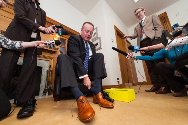 Kevin Doherty, Saskatchewan's minister of finance, puts on new shoes during a pre-budget Day photo opportunity at the Legislative Building in Regina, Saskatchewan on Tuesday May 31, 2016. Doherty will reveal the province's budget Wednesday, which is expected to include spending cuts. THE CANADIAN PRESS/Michael Bell