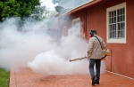 A Miami-Dade County mosquito control worker sprays around a home in the Wynwood area of Miami on Monday, Aug. 1, 2016. (AP Photo/Alan Diaz)