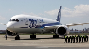 In this April 28, 2013 file photo, ground crewmen bow as a Boeing 787 'Dreamliner' of Japanese airline All Nippon Airways lands after a test flight at Haneda International Airport in Tokyo. (AP Photo/Shizuo Kambayashi, File)