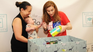 Jennifer Clary (right), co-founder and CEO of The Baby Box Co., presents a new mother with a Finnish-style baby box in Toronto, Ont. on Aug. 29, 2016. (Melissa Trainor/ The Baby Box Co.)