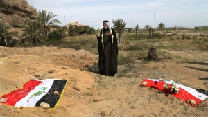 An Iraqi man prays for his slain relative at the site of a mass grave believed to contain the bodies of Iraqi soldiers killed by Islamic State group militants when they overran Camp Speicher military base in Tikrit, Iraq, in June 2014, in this photo taken on April 3, 2015. (AP / Khalid Mohammed)