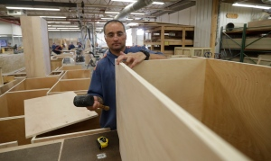 In a photo from Friday, July 8, 2016, inmate William Garrett works on a cabinet at the Habitat for Humanity Prison Build at the Ionia Correctional Facility in Ionia, Mich. Few states have been more aggressive in releasing inmates and diverting offenders than Michigan, where the prison system has long threatened the state's capacity to fund universities and other basics of government. (AP Photo/Carlos Osorio)