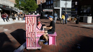 "In this Sunday, Sept. 25, 2016 photo Scott Frazer, of Medford, Mass., plays a piano on the sidewalk in the Harvard Square neighborhood of Cambridge, Mass. A number of working pianos painted by local artists have been placed around Boston and Cambridge, each with a simple message to passersby: ""Play Me, I'm Yours."" (Steven Senne/AP)"