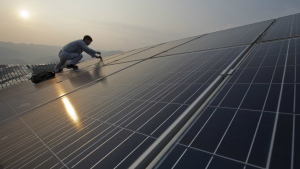 A worker performs maintenance work on solar panels at a photovoltaic power station in Songxi county in southeast China's Fujian province on Aug. 21, 2016. (Chinatopix)