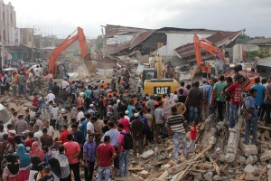 Rescuers use excavators to search for victims under the rubble of collapsed buildings after an earthquake in Pidie Jaya, Aceh province, Indonesia, Wednesday, Dec. 7, 2016. (AP Photo/Heri Juanda)