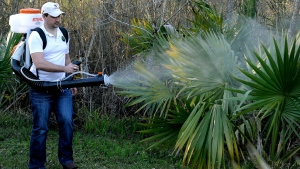 FILE- In this Feb. 10, 2016, photo, Darryl Nevins, sprays a backyard to control mosquitoes, in Houston, Texas. (AP Photo/Pat Sullivan)