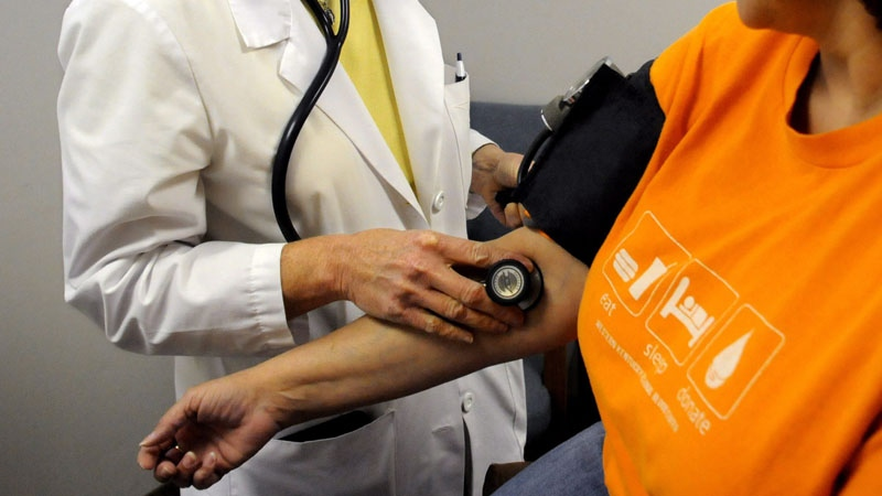 A nurse practitioner checks blood pressure during an annual check-up (The Messenger-Inquirer / Gary Emord-Netzley)